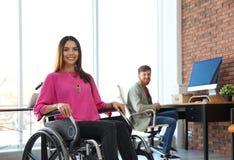 Jeune femme dans le fauteuil roulant avec le collègue photographie stock