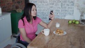 Jeune femme dans le fauteuil roulant parlant avec des amis employant l'Internet Ca banque de vidéos