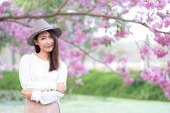 Jeune femme dans le jour de jardin de fleurs de cerisier au printemps Photos libres de droits