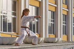 Jeune femme dans le kimono faisant l'exercice formel de karaté photographie stock libre de droits