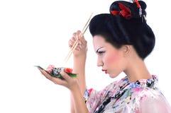 Jeune femme dans le kimono japonais avec les baguettes et le petit pain de sushi Photo stock