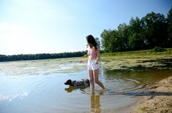 Jeune femme dans le lac avec le chien Images stock