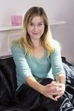 Jeune femme dans le lit à la maison photo stock