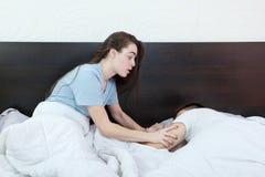 Jeune femme dans le lit avec l'expression triste et déçue sur son f Photos stock