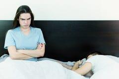 Jeune femme dans le lit avec l'expression triste et déçue sur son f Photographie stock libre de droits