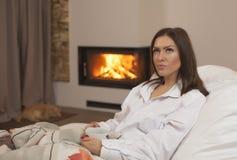 Jeune femme dans le lit buvant le chat et la cheminée chauds de sommeil de thé photographie stock