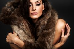 Jeune femme dans le lookin brun de manteau de fourrure à la caméra photographie stock