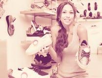 Jeune femme dans le magasin de chaussures Images stock