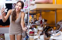 Jeune femme dans le magasin de chaussures Photos stock