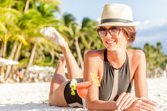 Jeune femme dans le maillot de bain avec le cocktail sur la plage dans le trop Photographie stock