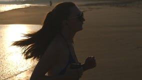 Jeune femme dans le maillot de bain fonctionnant sur la plage de mer et la musique de ?coute Silhouette de fille pulsant au rivag banque de vidéos