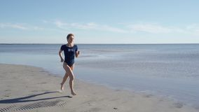Jeune femme dans le maillot de bain fonctionnant sur la plage de mer Fille pulsant le long du rivage d'oc?an Touriste f?minin aya clips vidéos