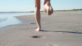 Jeune femme dans le maillot de bain fonctionnant sur la plage de mer Fille pulsant le long du rivage d'oc?an Touriste f?minin aya banque de vidéos