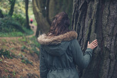 Jeune femme dans le manteau d'hiver par l'arbre Image stock