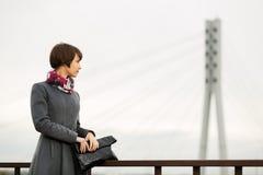 Jeune femme dans le manteau gris avec un sac à main Photographie stock libre de droits
