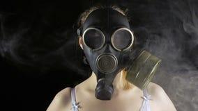 Jeune femme dans le masque et la fumée de gaz banque de vidéos