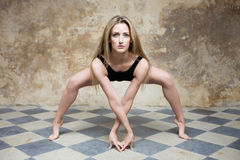 Jeune femme dans le noir dans la pose de yoga Photo stock