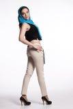Jeune femme dans le pantalon beige, gilet noir avec l'écharpe bleue Photos stock