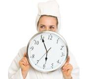 Jeune femme dans le peignoir se cachant derrière l'horloge Photo stock