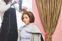 Jeune femme dans le salon de coiffure photos stock