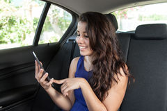 Jeune femme dans le siège arrière de la voiture souriant et lisant l'ebook Images stock