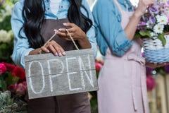 Jeune femme dans le signe ouvert de participation de tablier tout en se tenant dans le fleuriste Image stock