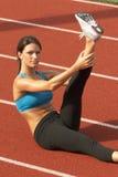 Jeune femme dans le soutien-gorge de sports étirant la patte dans le ciel sur la piste Photos libres de droits
