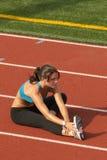 Jeune femme dans le soutien-gorge de sports étirant le tendon du jarret sur la piste Images libres de droits