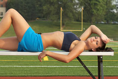 Jeune femme dans le soutien-gorge de sports s'étendant sur le banc Image libre de droits