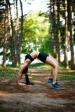 Jeune femme dans le sportwear faisant la force exercée en parc d'été Extérieur d'exercice de sport images stock