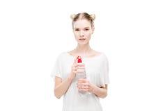 Jeune femme dans le T-shirt blanc tenant la bouteille avec de l'eau et regardant l'appareil-photo photographie stock libre de droits