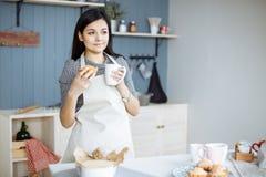Jeune femme dans le tablier appréciant le café ou le thé dans la cuisine photos stock