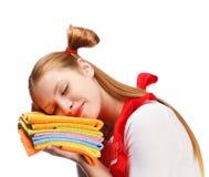 Jeune femme dans le tablier rouge dormant sur la pile des serviettes de thé colorées Photos stock