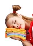 Jeune femme dans le tablier rouge dormant sur la pile des serviettes de thé colorées Photographie stock libre de droits