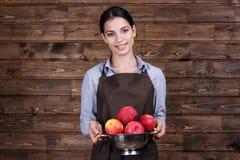 Jeune femme dans le tablier tenant la passoire avec les pommes juteuses Image stock