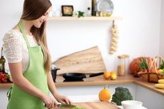 Jeune femme dans le tablier vert faisant cuire dans la cuisine Femme au foyer coupant en tranches la salade fraîche Photo stock