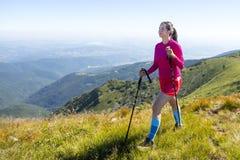 Jeune femme dans le trekking rose dans la montagne Photo libre de droits