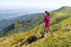 Jeune femme dans le trekking rose dans la montagne Photo stock