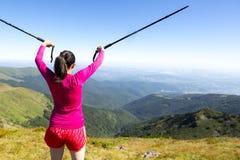 Jeune femme dans le trekking rose dans la montagne Photos stock