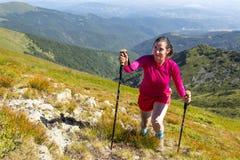 Jeune femme dans le trekking rose dans la montagne Images stock