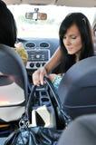 Jeune femme dans le véhicule atteignant le sac à main Photo libre de droits