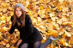 Jeune femme dans les couleurs vibrantes d'automne de stationnement image stock