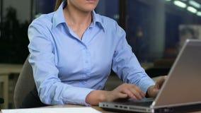 Jeune femme dans les emails formels d'ordinateur portable et de lecture d'ouverture de costume, fonctionnant la nuit banque de vidéos