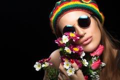 Jeune femme dans les lunettes de soleil et le chapeau de rasta tenant des fleurs Images libres de droits