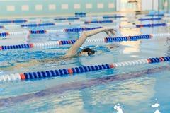 Jeune femme dans les lunettes et chapeau nageant le style de course de rampement avant dans la piscine d'intérieur de course de l Images stock