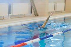 Jeune femme dans les lunettes et chapeau nageant le style de course de rampement avant dans la piscine d'intérieur de course de l Photos stock