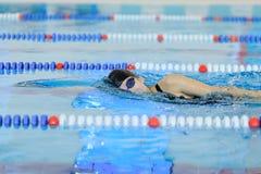 Jeune femme dans les lunettes et chapeau nageant le style de course de rampement avant dans la piscine d'intérieur de course de l Photo stock