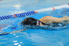 Jeune femme dans les lunettes et chapeau nageant le style de course de rampement avant dans la piscine d'intérieur de course de l Photographie stock