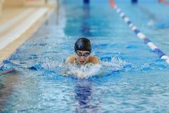 Jeune femme dans les lunettes et style de course de brasse de natation de chapeau dans la piscine d'intérieur de course de l'eau  Photo stock