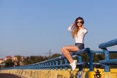 Jeune femme dans les mini-shorts et la chemise blanche Photographie stock libre de droits